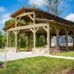 wooden pavilion sitting beneath blue sky and in front of newly built home and tree line
