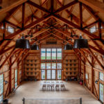 timber frame party barn with large windows and wood floor