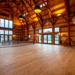 timber frame party barn interior with tennis net and basketball hoop