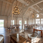 timber frame wedding venue with ornate tables and chairs along with hanging lights