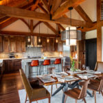 contemporary kitchen sitting next to dining room furniture beneath large timber frames