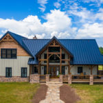timber frame home with metal roof and stone stone walkway leading to front door
