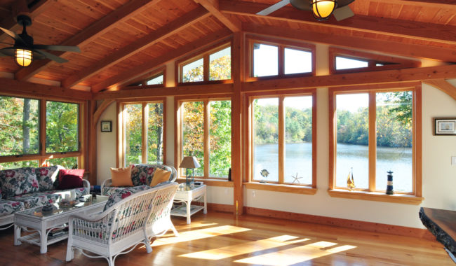 timber frame sunroom with polished wood floor and large windows overlooking body of water in maryland