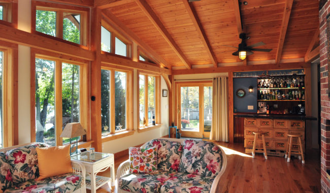 timber frame sunroom with floral designed furniture and large windows