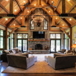 timber frame truss ceiling sitting above stone fire place and living room decor