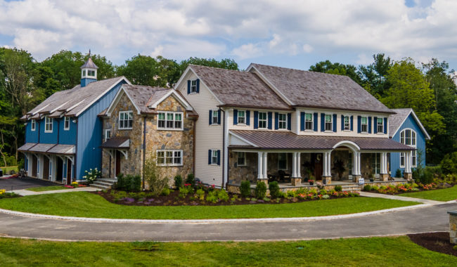 large picturesque home with front lawn flower bed and rear tree line in menham new jersey