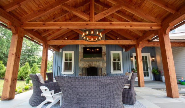 douglas fir trusses in outdoor living space with living room furniture sitting beneath it