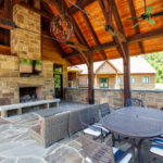 timber frame truss ceiling overlooking outdoor dining and fireplace pit