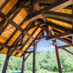 timber frame trusses supporting light brown roof beneath blue skies and green trees