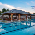 outdoor pool pavilion with wooden beams and metal roof overlooking swimming pool