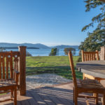 lake view from backyard patio of vacation home with wood tables and chairs