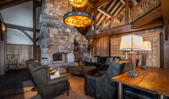 vintage style living room with large stone chimney and black and brown leather chairs