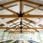 elementary school cafeteria with timber frame truss ceiling and white walls