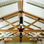 white ceiling with symmetrical timber frame trusses and black light