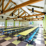timber frame truss roof in cafeteria with multi colored tables and floor
