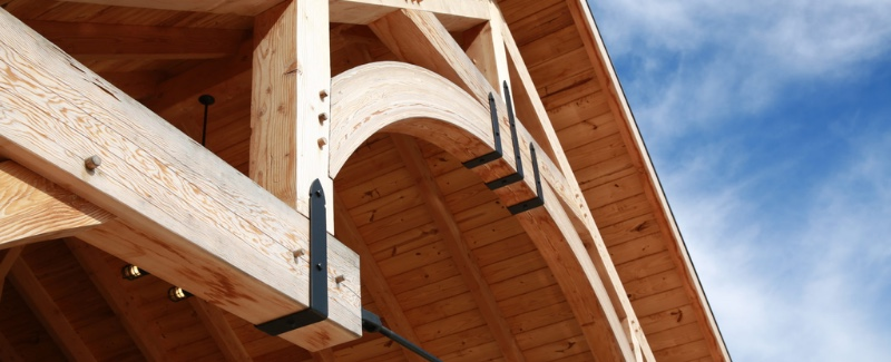 timber frame structure with black brackets sitting beneath blue sky